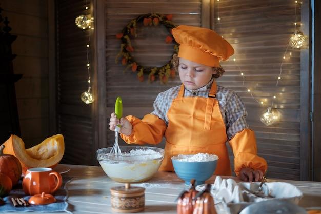 オレンジ色のシェフの衣装を着たかわいい縮れ毛の少年は、感謝祭のためにパンプキンパイを準備しています。家族の休日の伝統