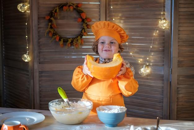 オレンジ色のシェフの衣装を着たかわいい縮れ毛の少年は、感謝祭のためにパンプキンパイを準備しています。家族の休日の伝統 Premium写真