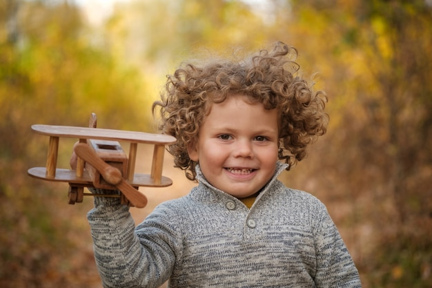 Cute curly haired boy playing with wooden plane in autumn park