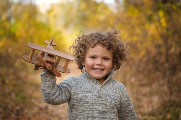 秋の公園で木製の飛行機で遊ぶかわいい縮れ毛の少年