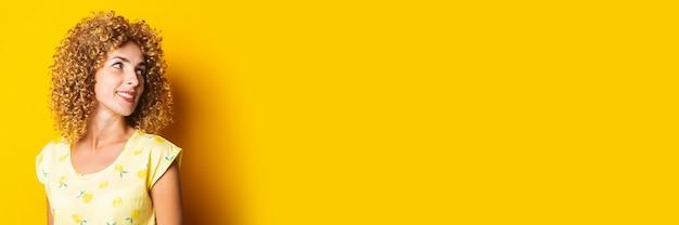 笑顔のかわいい縮れ毛の女の子は黄色の背景に横に見えます