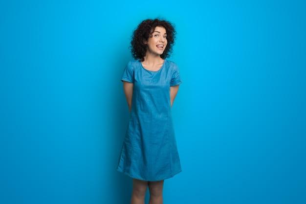 ドレスを着てかわいい巻き毛の髪の女性が幸せを身振りで示す青い壁にポーズをとっている