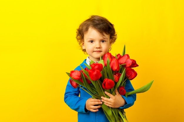 Cute curly smiling boy  with a bouquet of red tulips for mom. mothers day.