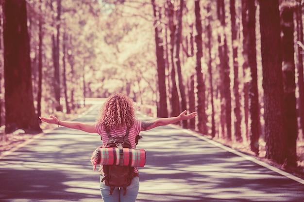 Симпатичная кудрявая путешественница кавказская молодая женщина смотрит со спины посреди дороги с высокими деревьями по обеим сторонам, открывая руки и наслаждаясь свободой и независимостью путешествий