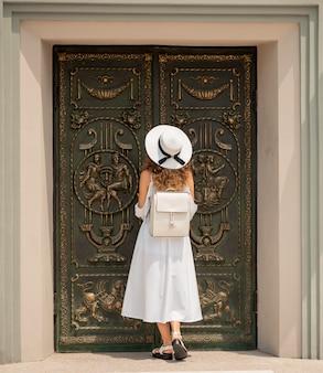 古代の彫刻が施されたドアが付いている寺院にアクセスするかわいい巻き毛の女性