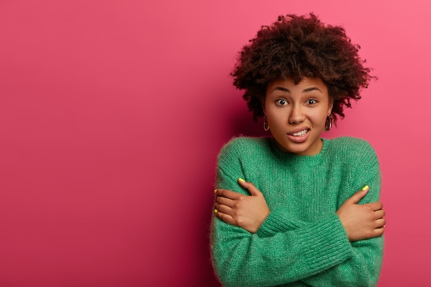 Cute curly woman crosses arms over body, trembles during freezing cold winter weather