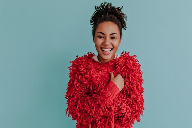 赤いジャケットでポーズをとってかわいい巻き毛の女性