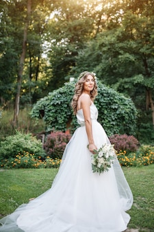 A cute curly woman in a white wedding dress with a wedding bouquet