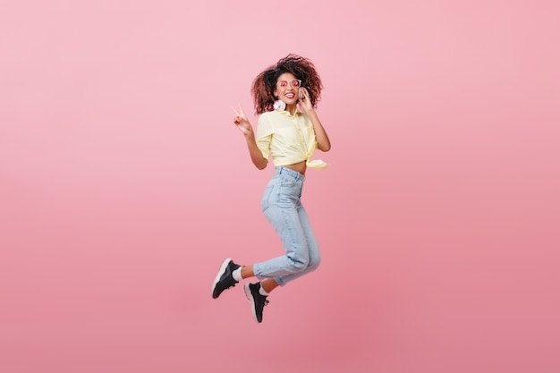 Cute curly woman in yellow shirt expressing happy emotions with smile. magnificent african hipster girl jumping.