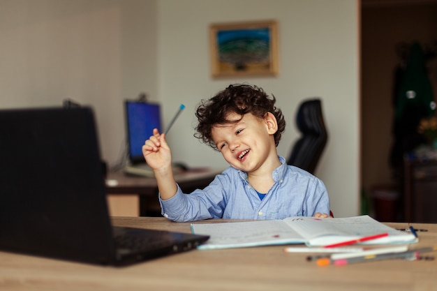 A cute curlyhaired kid sits at his laptop at the table the preschool age