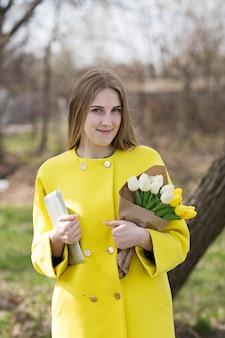 Cute cute girl with long hair in a yellow coat.