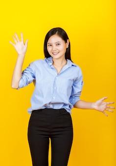 캐주얼한 긴팔 셔츠를 입은 아름다운 아시아 여성의 귀여운 컷아웃 초상화는 재미있는 사무총장으로 웃고, 10가지 놀라운 사업 판촉과 행복한 거래를 표현하기 위해 손짓을 합니다.