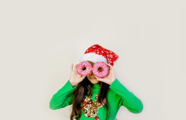 サンタの帽子をかぶったかわいい黒髪の女の子が笑って、楽しんで、彼女の目に2つのドーナツを通して見ています。