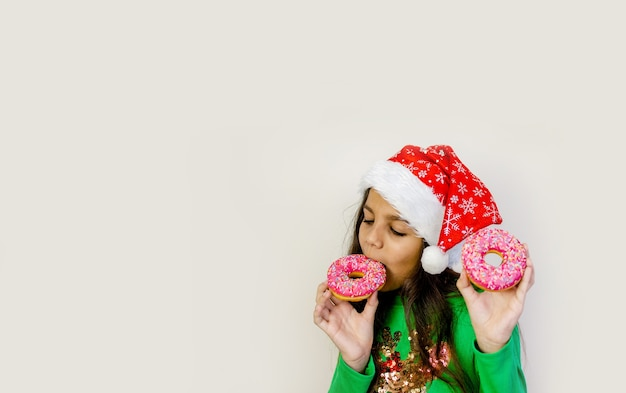 サンタの帽子をかぶったかわいい黒髪の女の子が笑って、楽しんで、彼女の目に2つのドーナツを味わっています。
