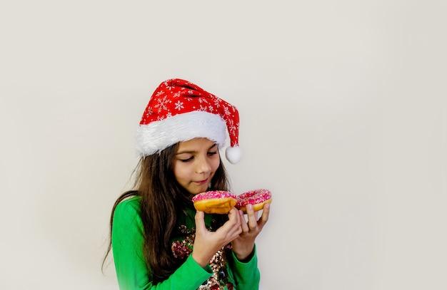 웃 고, 재미와 그녀의 눈에 두 도넛을 시음 산타 모자에 귀여운 검은 머리 소녀.