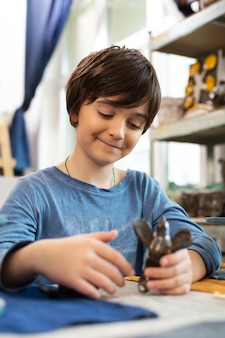 Cute dark-haired boy playing before modeling figures with clay