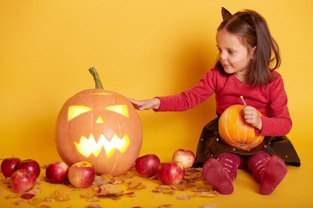 Милая темноволосая девушка сидит на полу с ужасающей резной тыквой на хэллоуин