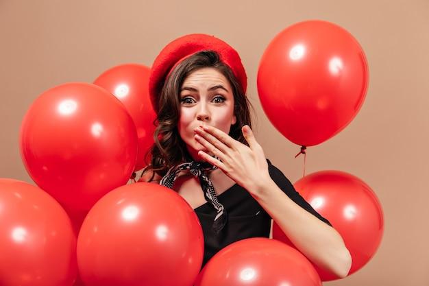Carina signora dai capelli scuri guarda felicemente nella fotocamera e soffia bacio su sfondo beige con palloncini rossi.