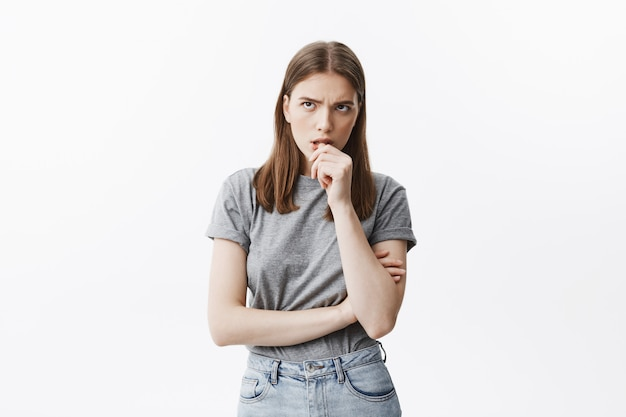 Cute dark-haired unhappy student girl in grey t-shirt gnaws fingers, looking aside with agitated look, can't relax waiting for results of test in university.