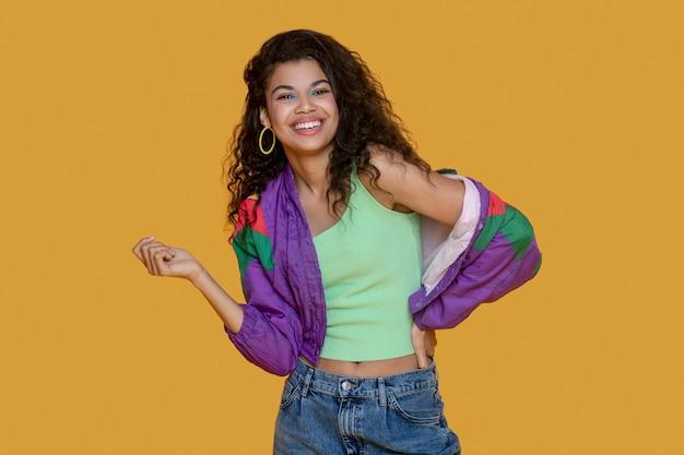 Симпатичная темноволосая молодая женщина в ярком пиджаке выглядит радостной