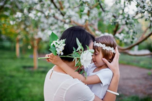 花の春の庭で抱き締めるかわいい娘と母幸せな女性と子供、屋外で白いドレスを着て、春の季節が来ています。母の日の休日の概念