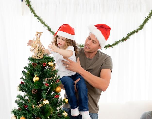 Симпатичная дочь, украшающая елку с отцом