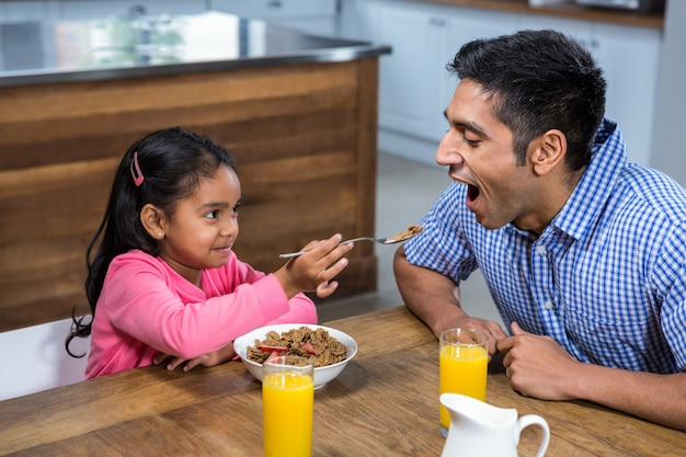 Cute daughter feeding his father