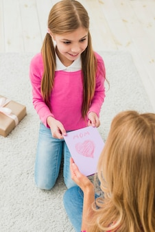 Cute daughter giving greeting card to mother