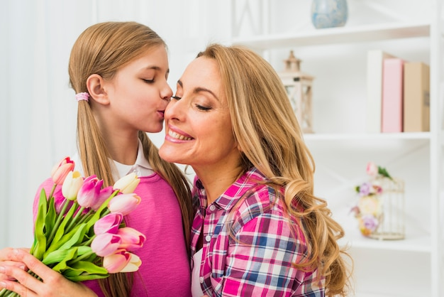 Cute daughter kissing mother with tulips