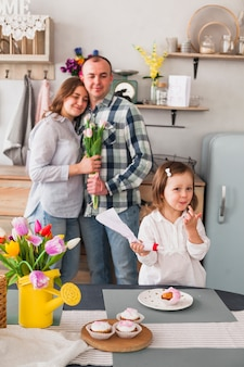 Cute daughter making cupcake near parents with flowers