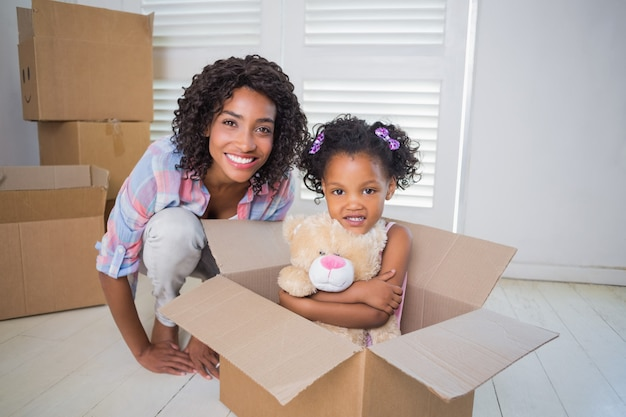 Cute daughter sitting in moving box with mother