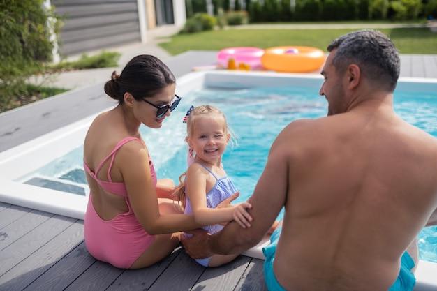 웃는 귀여운 딸. 엄마 아빠와 함께 수영장 근처에서 쉬면서 웃고 있는 사랑스러운 귀여운 딸
