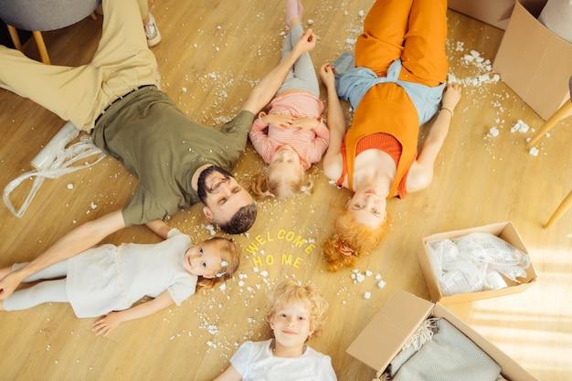 両親と床に横たわって喜んでいるかわいい子供たち