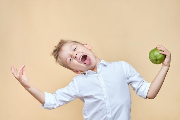かわいい乱れた少年は、梨を手に持って耽溺し、しかめっ面をします。
