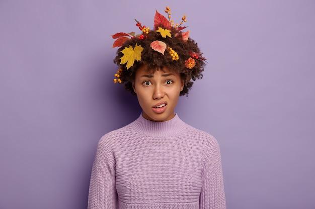 かわいい不満のアフリカ系アメリカ人の女性は顔を笑い、唇をすぼめ、悲しい表情をしており、紫色で分離された髪のニットのセーターに黄色の葉と果実を着ています。