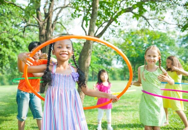 Симпатичные разнообразные дети, играющие с обручами