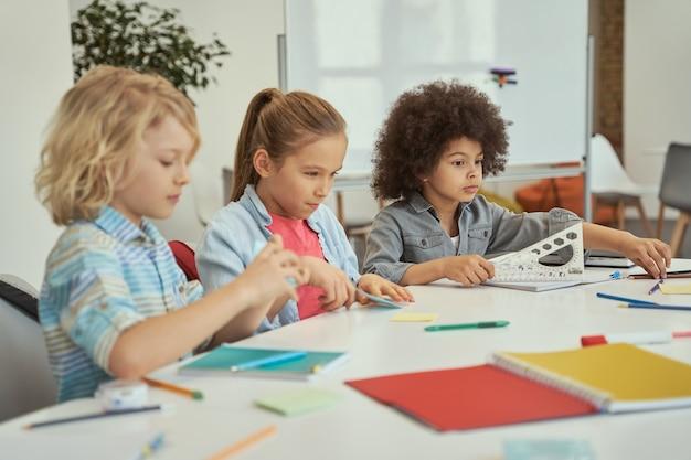 Симпатичные разные дети сидят вместе за столом во время учебы в классе начальной школы