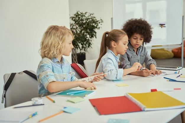 Симпатичные разнообразные дети учатся и рисуют, сидя вместе за столом в начальной школе