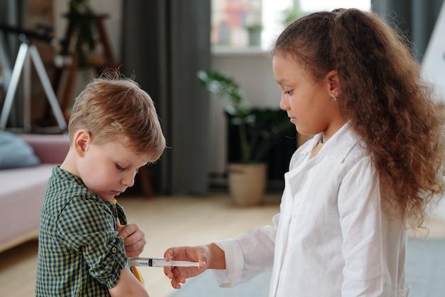 遊びの間に小さな男の子に注射をするかわいい医者または看護師