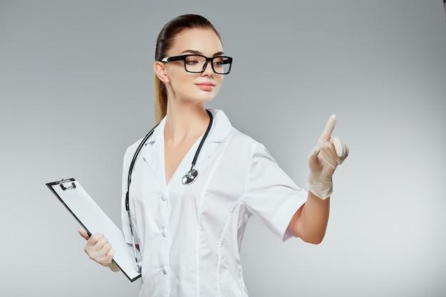 Милый доктор с каштановыми волосами и обнаженным макияжем в белой медицинской форме, очках, стетоскопах и белых перчатках на сером фоне студии и указывая пальцем, держа примечания.