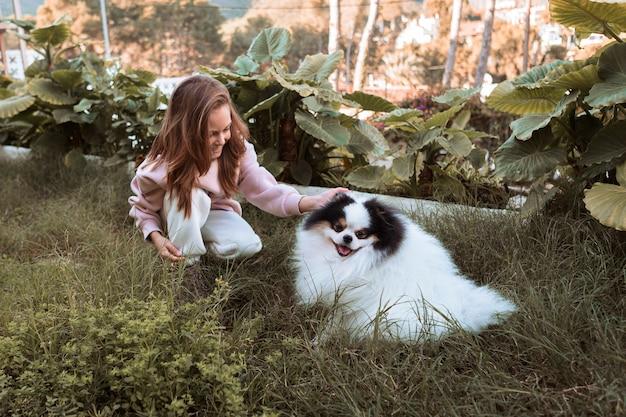 Милая собака и девочка играют в саду