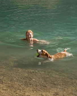 Милая собака держит мяч и плавает рядом со своим владельцем
