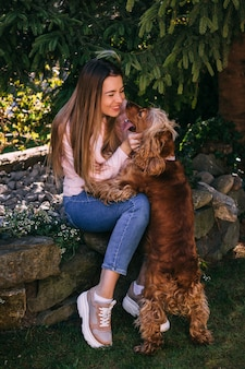 Cute dog kissing young woman - true friend concept