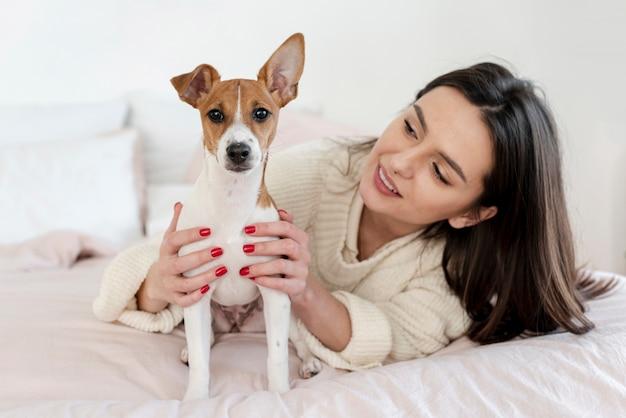 Милая собака позирует в то время как проводится женщиной