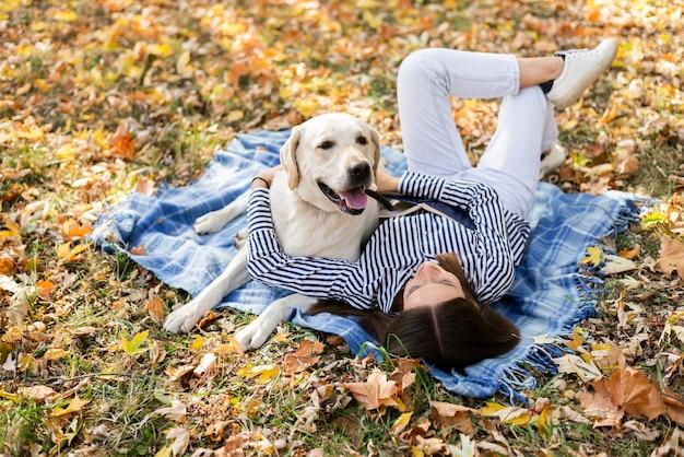 Милая собака с молодой женщиной, сидя на одеяле