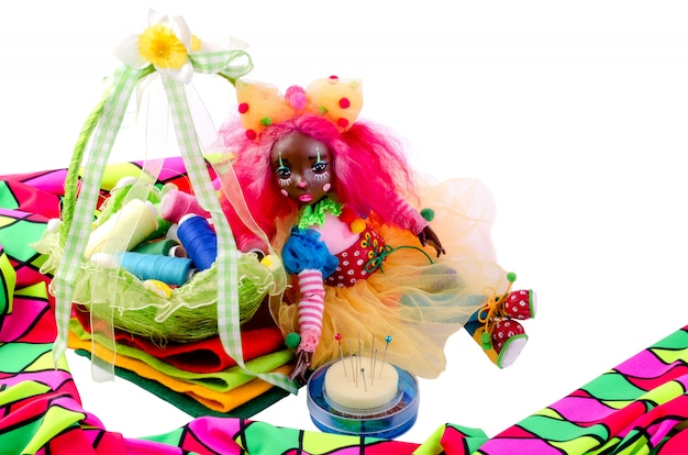 Cute doll sits from above to pieces of colorful cloth, next to it pins, multicoloredcloth.