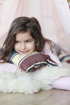 Милая девушка мечтает, лежа на подушке