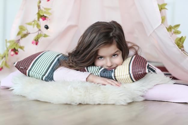 Ragazza carina di sogno sdraiato sul cuscino e alla ricerca