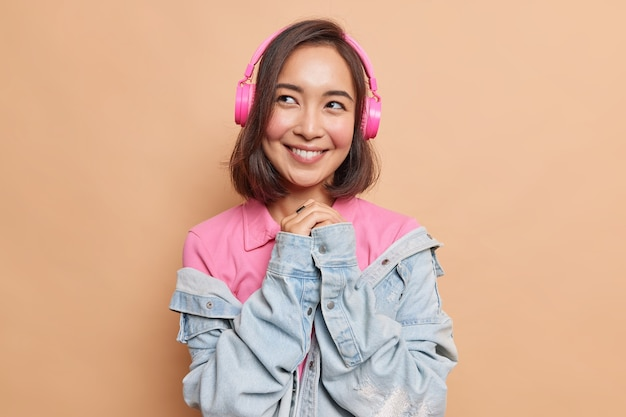 Cute dreamy asian woman keeps hands pressed together thinks about something pleasant enjoys best music app on modern device good sound quality wears casual t shirt denim jacket isolated on beige wall