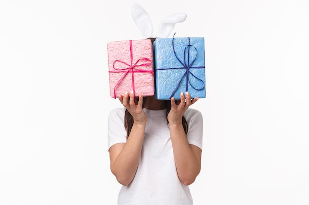 Cute easter bunny female in rabbit ears, hiding her face behind pastel wrapped gift boxes